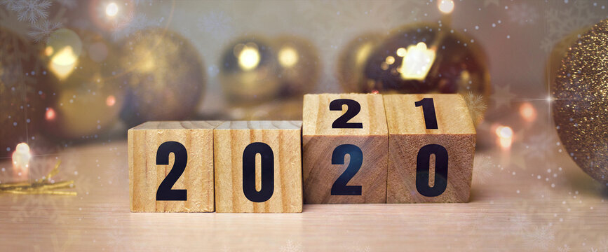 Business and design concept - surreal abstract geometric floating wooden cube with word 2020 2021 concept on wood floor and christmas background