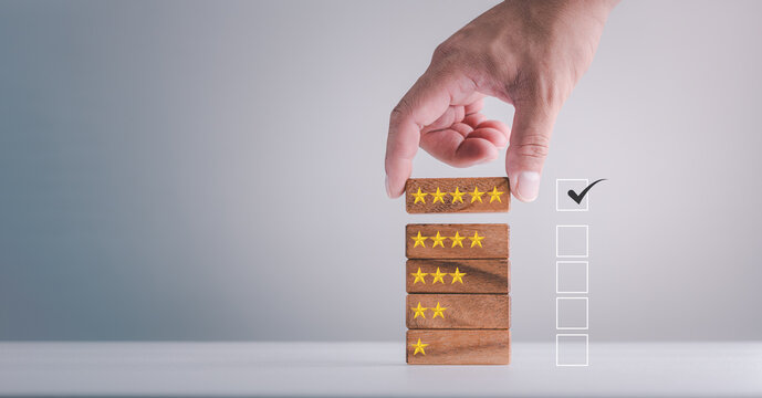 feedback rating and positive customer review experience, service and Satisfaction, Business people are Choosing wood block with 5 star icon to give satisfaction in service. rating very impressed.