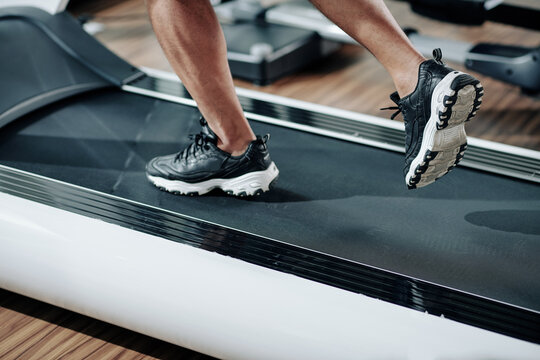 Close-up image of fit man in sneakers running fast on treadmill in gym in the morning