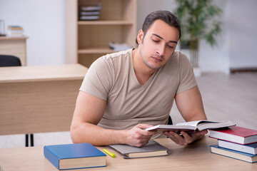 Young male student preparing for exams at library