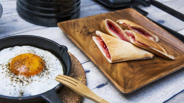 目玉焼きと苺ジャムのホットサンドのアウトドアな朝ごはんのイメージ
