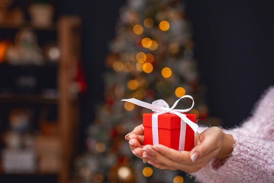 woman gives a Christmas gift box by holding it forward. Close up.