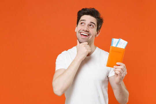 Pensive young traveler tourist man in white t-shirt hold passport ticket put hand prop up on chin isolated on orange background. Passenger traveling on weekend getaway. Air flight journey concept.