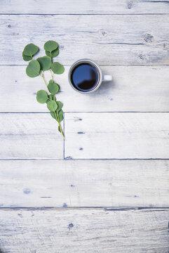 白い木製テーブルと白いカップに入ったホットコーヒー