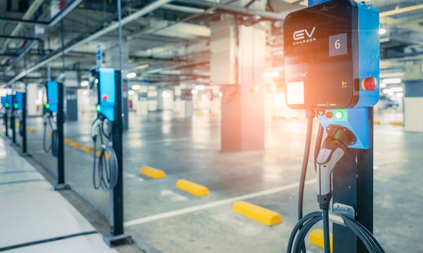 Electric car charging station for charge EV battery. Plug for vehicle with electric engine. EV charger. Clean energy. Charging point at car parking lot. Green power. Future transport technology.