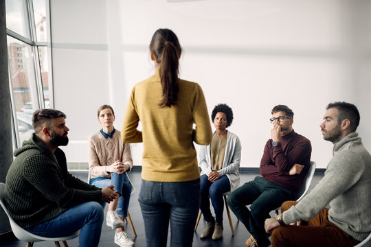 Group of people attending a therapy and listening to one of the participants.