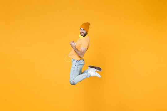 Full length side view of joyful young man 20s wearing basic casual t-shirt headphones hat jumping doing winner gesture looking camera isolated on bright yellow colour background, studio portrait.