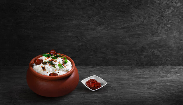 Vegetarian meal creamy tasty curd rice with spices topping served in clay pot and lemon pickle on black textured background  thayir sadam