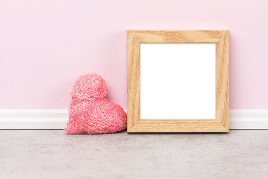 Minimalist background template, square wooden picture frame and heart-shaped ornament in front of pink wall. Blank image area isolated with clipping path.