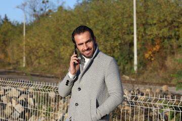 Stylowo ubrany przystojny, dojrzały  mężczyzna z telefonem na peronie.