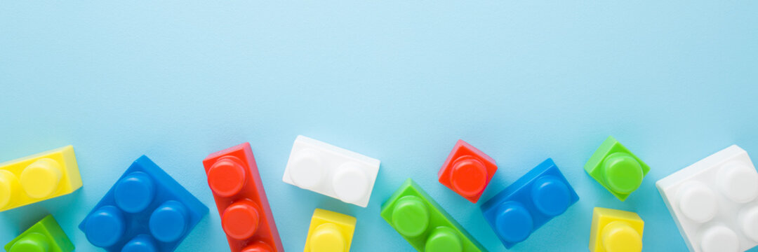 Colorful bright plastic blocks on light blue table background. Pastel color. Closeup. Toys of development for little kids. Empty place for text. Wide banner. Top down view.