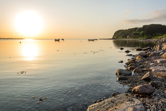 Beautiful sunrise over peaceful bay at the Baltic Sea with small boats and rocky shore
