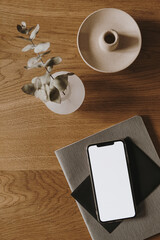 Flatlay of blank screen smart phone, notebook, eucalyptus branch on wooden background. Home office desk workspace. Business, work template. Flat lay, top view.