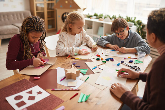 Multi-ethnic group of children making handmade Christmas cards together while enjoying art and craft class, copy space