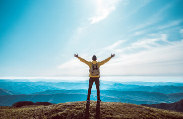 Successful man with arms up on the top of the mountain - Hiker on the cliff raising hands to the sky.