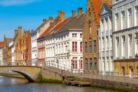 Bruges, Belgium street view panorama with canal and colorful traditional houses against blue sky in popular belgian destination,