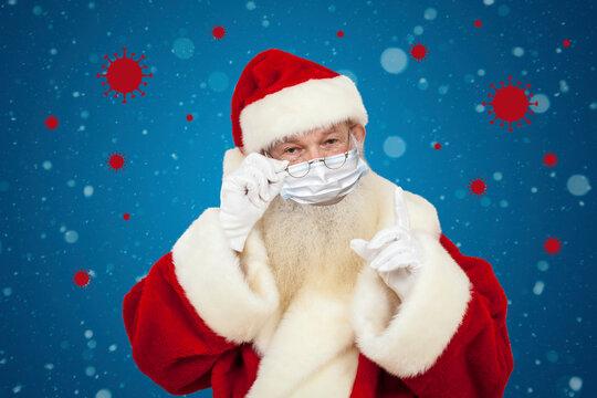 Weihnachtsmann mit Maske und Corona Viren im Hintergrund