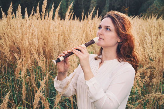 A flute player holds a black flute while standing in the autumn field