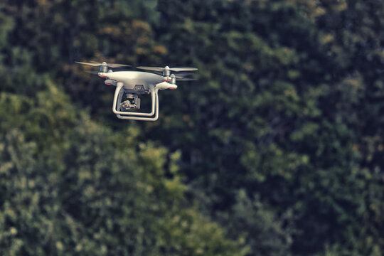 An aerial drone with a camera flies and shoots video over the forest