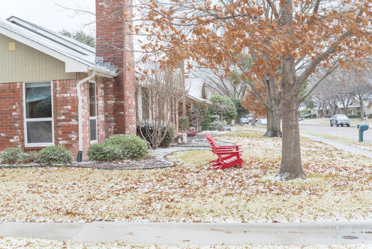 Suburban house with brick chimney and red adirondack chairs at front yard in snow covered in Texas, USA