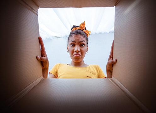 Sad upset african woman unpacking damaged carton box