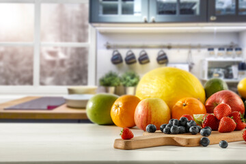 Fresh fruit in the kitchen on a wooden table by the sunny window