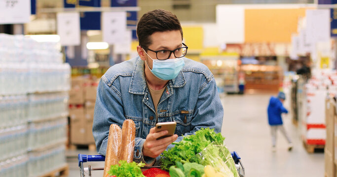 Portrait of handsome Caucasian male customer in glasses in supermarket with shopping cart full of food products typing on smartphone. Man client in mask buying food at grocery and texting on cellphone
