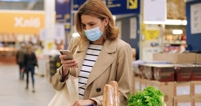 Camera approaching Caucasian young beautiful woman in mask in supermarket checking shopping list on smartphone with food products in shopping cart. Female tapping on cellphone in grocery. Close up