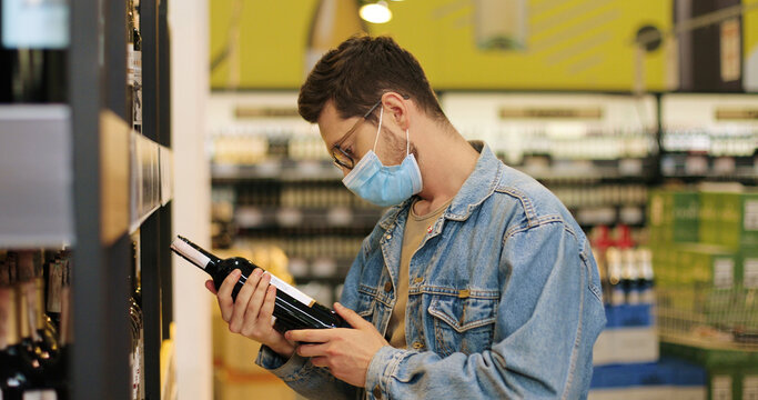 Side view of happy Caucasian young man in glasses on shopping taking photo of bottle of wine on smartphone at supermarket. Handsome male in mask choosing drink. Close up portrait concept