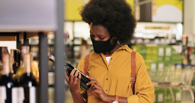 Close up portrait of young African American woman in mask choosing bottle of wine from shelf in food supermarket. Pretty female customer buying drink in supermarket. Side view. Buyer concept