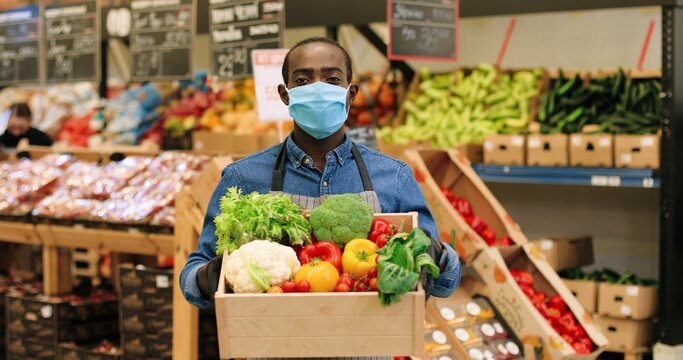 Portrait of joyful male food store manager in mask and gloves standing in supermarket and holding box with fresh vegetables, looking at camera and smiling. African American mam working at grocery.