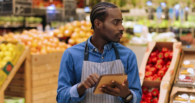 Close up portrait of busy African American male worker standing in supermarket and typing on tablet while doing inventory. Young man food store assistant at work tapping on device. Retail concept