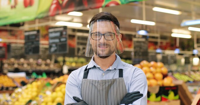 Close up portrait of cheerful young male supermarket employee in face shield looking at camera and smiling. Caucasian handsome happy man at work in grocery in vegetable sector. Retail concept