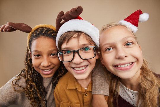 Close up portrait of three children wearing Christmas portraits and smiling at camera while standing against beinge background in studio