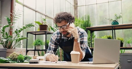 Fototapeta Happy Caucasian businessman talking on cellphone while standing in apron in small floral center and writing down order details. Joyful male florist calling on smartphone at work. Own business concept obraz