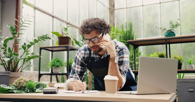 Happy Caucasian businessman talking on cellphone while standing in apron in small floral center and writing down order details. Joyful male florist calling on smartphone at work. Own business concept