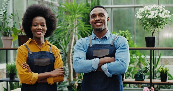 Portrait of happy man and woman in aprons standing at own small flower shop and smiling to camera after reopening African American joyful couple entrepreneurs running own floral business Store concept