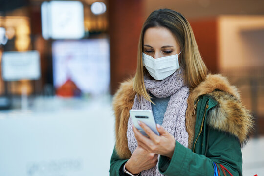 Portrait of adult woman shopping in mall using smartphone wearing a mask
