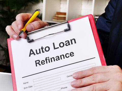 Auto loan refinance concept. The man offers to sign the document.