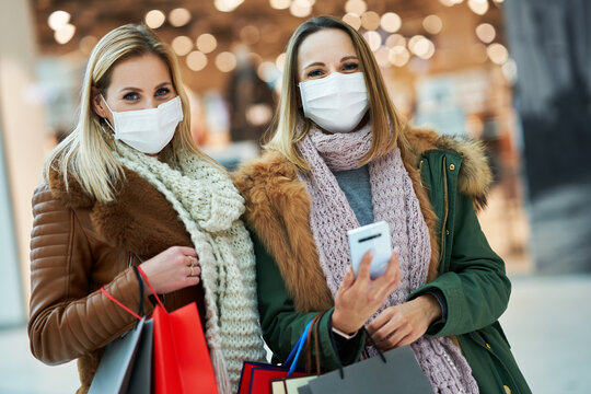 Girl friends with smartphone shopping together wearing mask coronavirus concept