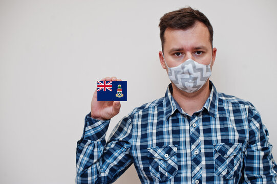 Man in checkered shirt show Cayman Islands flag card in hand, wear protect mask isolated on white background. American countries Coronavirus concept.