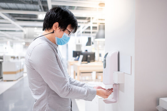 Asian man using automatic alcohol dispenser for cleaning hand in office. Infection prevention concept. Save and clean in public building.