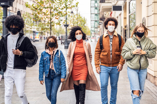 Group of multiracial friends walking on city street with protective face mask.