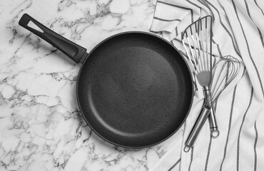 Frying pan, cooking utensils and tablecloth on white marble background, flat lay