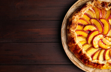 Delicious fresh peach pie on wooden table, top view. Space for text
