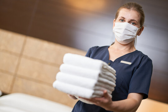 Chambermaid in mask holding stack of clean towels in bedroom
