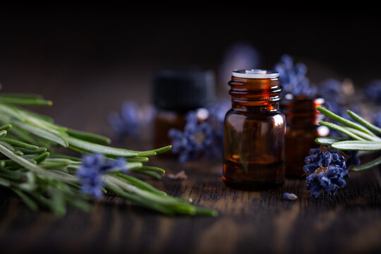 Rosemary and lavender essential oils in dark glass bottles on wood