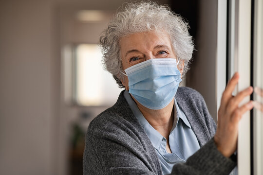 Happy senior woman wearing surgical mask at home