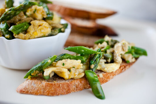 Close up of bruschetta with scrambles eggs and asparagus