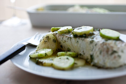 Plate of cooked fish with cucumber slices